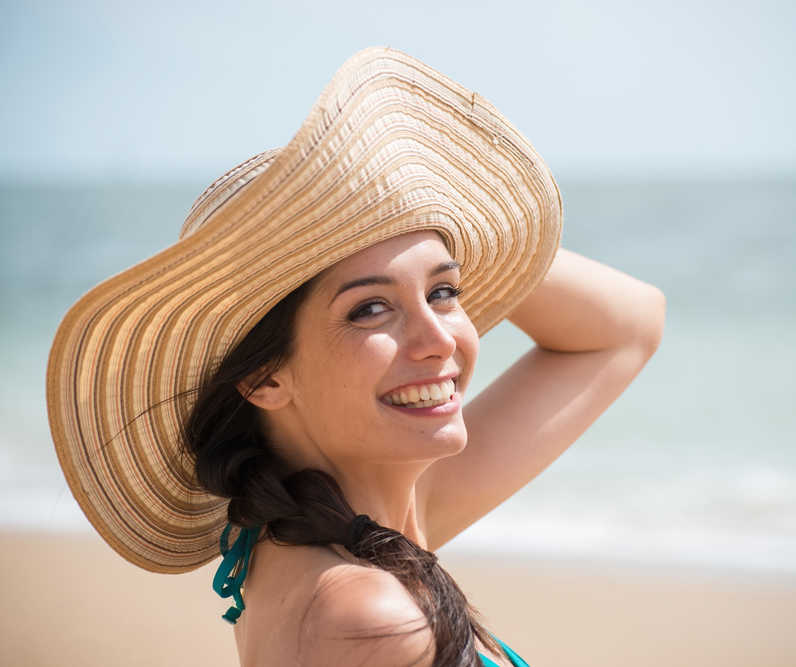 woman with pretty skin wearing a hat at the beach | Hypo & Hyperpigmentation | Why Some People Get Skin Color Changes With Skin Treatments [Free Infographic] | Masterpiece Skin Restoration