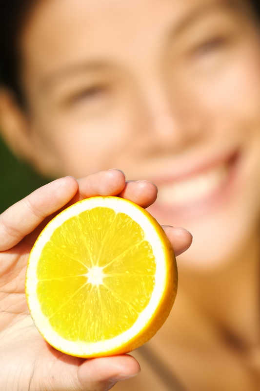 blurred face with closeup of lemon full of vitamin C | How Vitamins C and E Work Together to Fight Skin Damage! | Masterpiece Skin Restoration