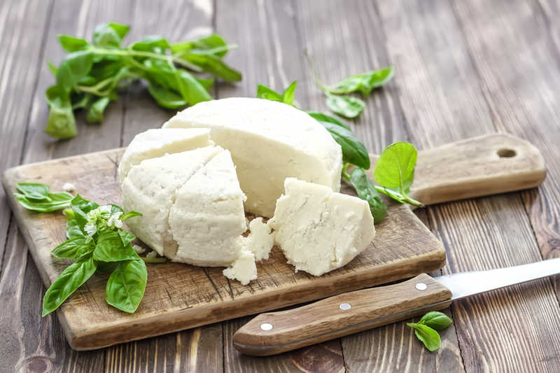cheese and basil on a cutting board next to knife | 17 of the Best Ways to Treat Adult Acne! | Masterpiece Skin Restoration