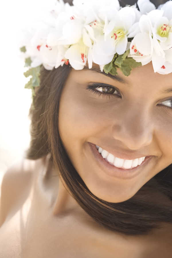 beautiful young woman with medium tone skin and flowers in her hair smiling