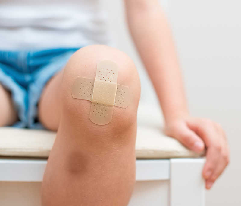 closeup of boy's knee with bandaids