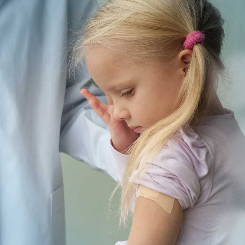 little girl with long blonde hair crying, medical professional in the background
