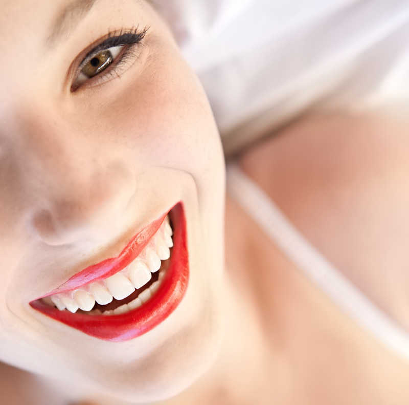 smiling woman with beautiful lips wearing red lipstick looking up