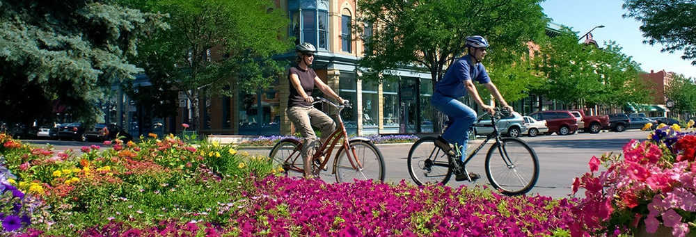 beautiful old town Fort Collins, Colorado with people cycling and blooming flowers