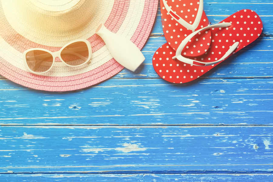 hat, sunglasses, flip flops, sunscreen on blue wood background | Melasma Treatment | 11 Things That Really Work! | Masterpiece Skin Restoration