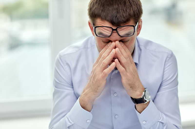 man with glasses rubbing his face, looking stressed