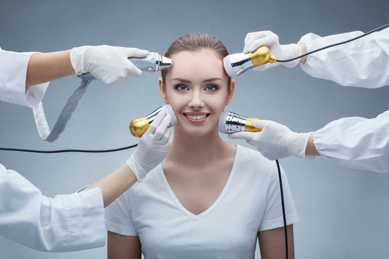 smiling woman getting different kinds of skin rejuvenation treatments applied to her face