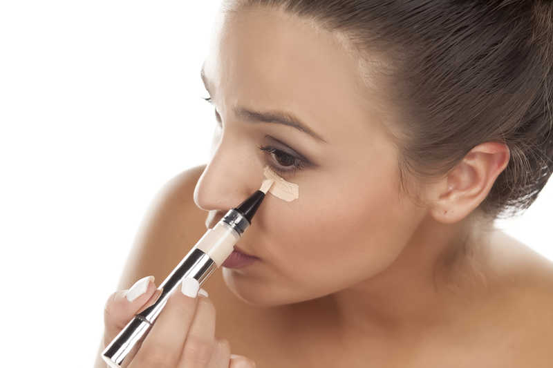 woman with beautiful skin applying concealer under her eyes