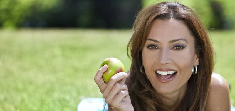 beautiful mature woman eating a green apple, long brown hair