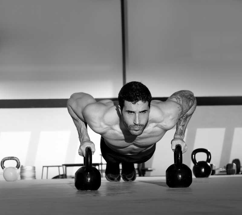 black and white of man doing push ups using kettle bells
