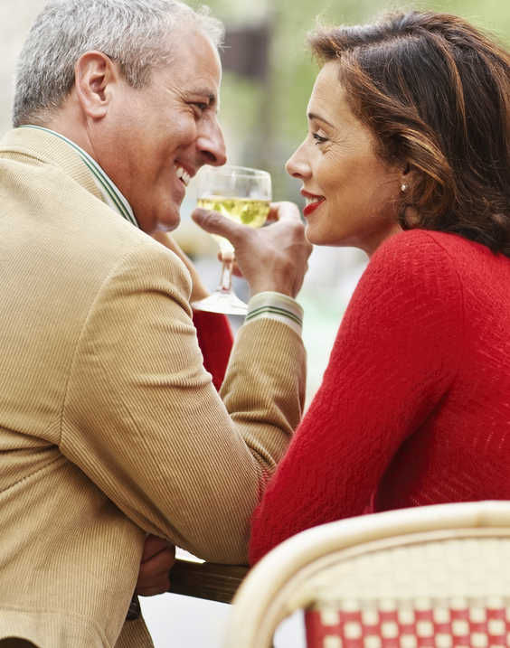 man with receding hairline having drinks with a smiling woman wearing red