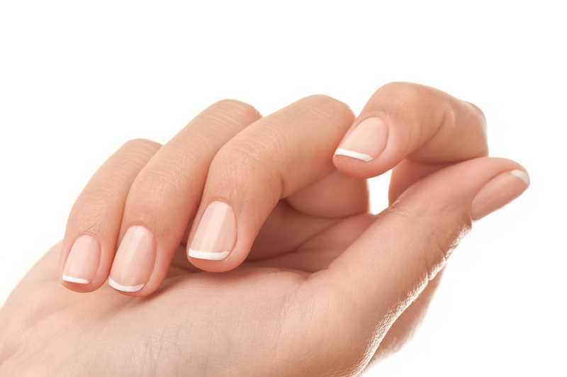 closeup of woman's hand with french manicure | 15 Steps to Beautiful, Healthy Nails! | Masterpiece Skin Restoration