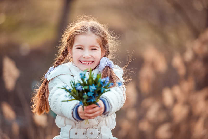 pretty little girl with braids holding a bouquet of blue flowers
