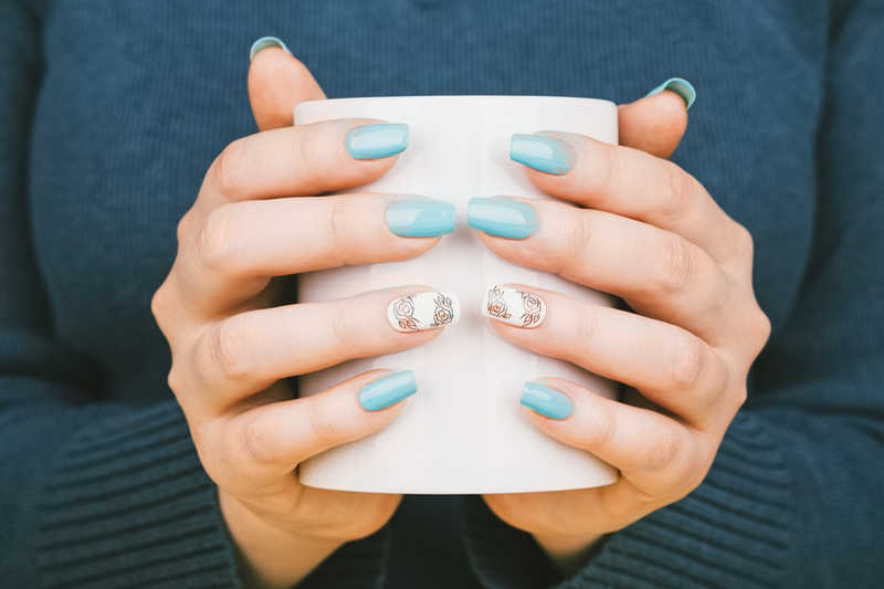 woman's hands with blue polish holding a coffee mug | 15 Steps to Beautiful, Healthy Nails! | Masterpiece Skin Restoration