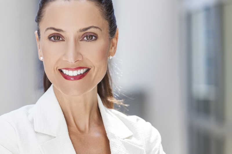 beautiful mature business woman wearing a white suit, hair in a ponytail, smiling