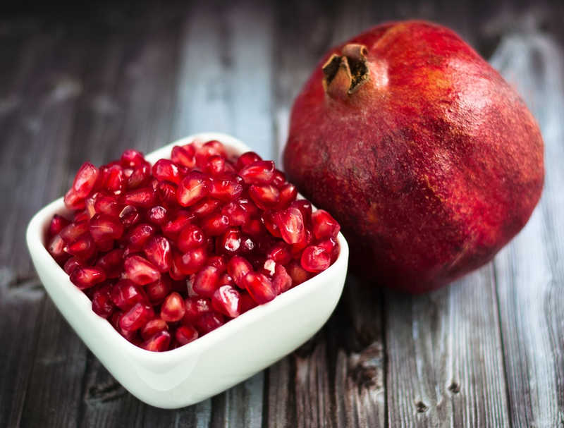 pomegranate and bowl of seeds on a wood counter
