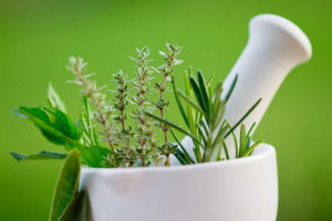 herbs in a mortar and pestle green background