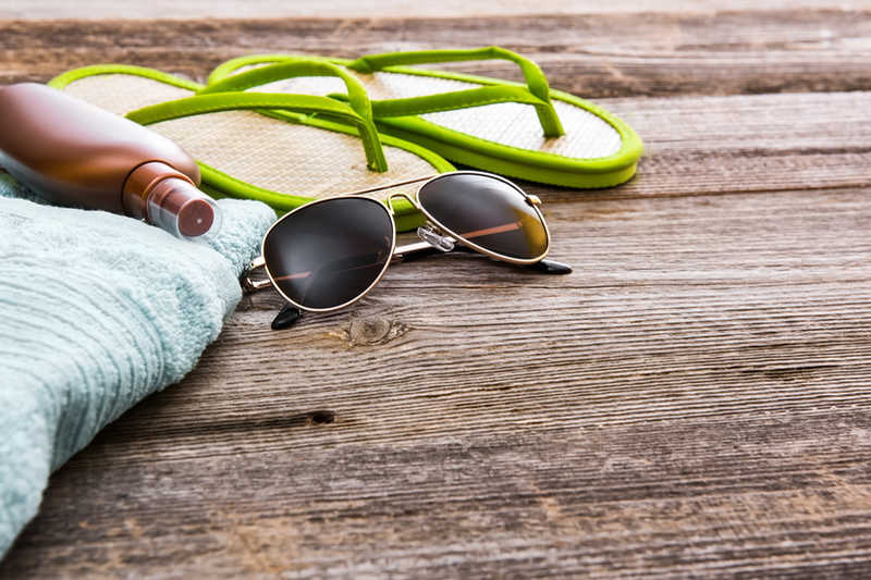 sunglasses, green sandals, towel and sunscreen on brown deck | Physical Sunscreen vs. Chemical | Which Is Better? | Masterpiece Skin Restoration