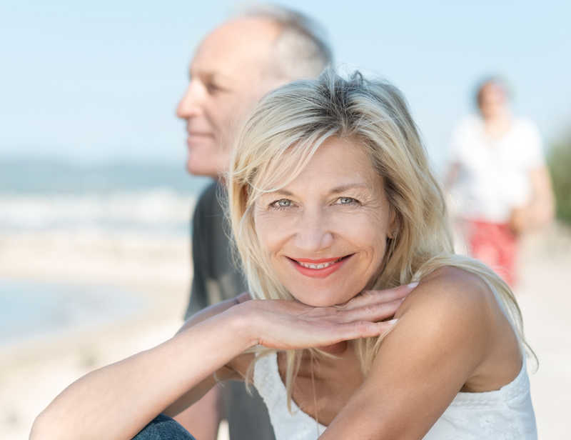 mature smiling woman wearing a tank top with her husband at the beach | Eye Rejuvenation | 21 Methods That REALLY Work! | Masterpiece Skin Restoration