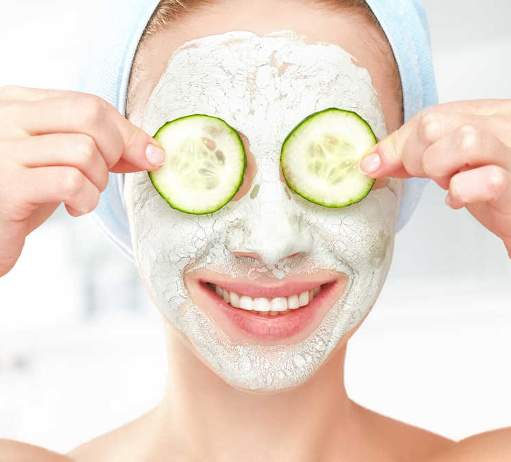 woman with mask holding cucumber slices up to her eyes, smiling | Eye Rejuvenation | 21 Methods That REALLY Work! | Masterpiece Skin Restoration