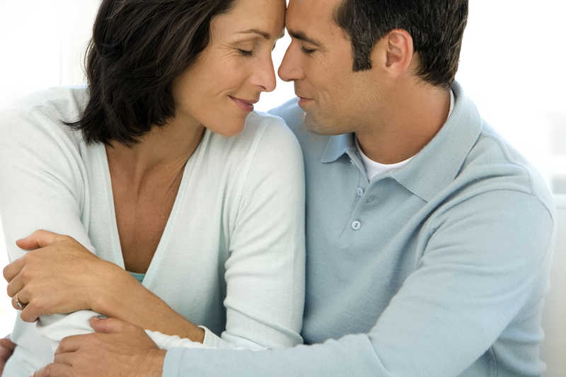 attractive mature couple forehead to forehead wearing light blue