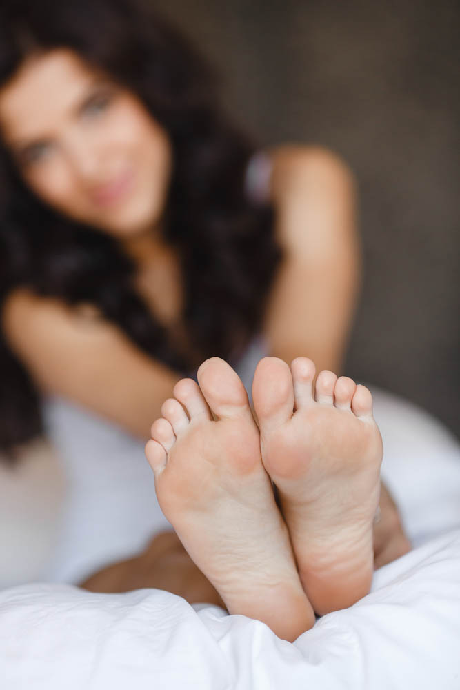 pretty girl with long dark hair sitting in bed, closeup of her feet