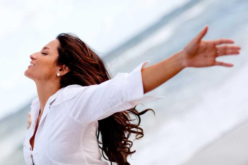 pretty woman, long dark hair, eyes closed, white blouse, hands in the air