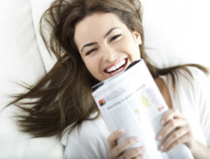 Smiling young woman with long dark hair reading a magazine