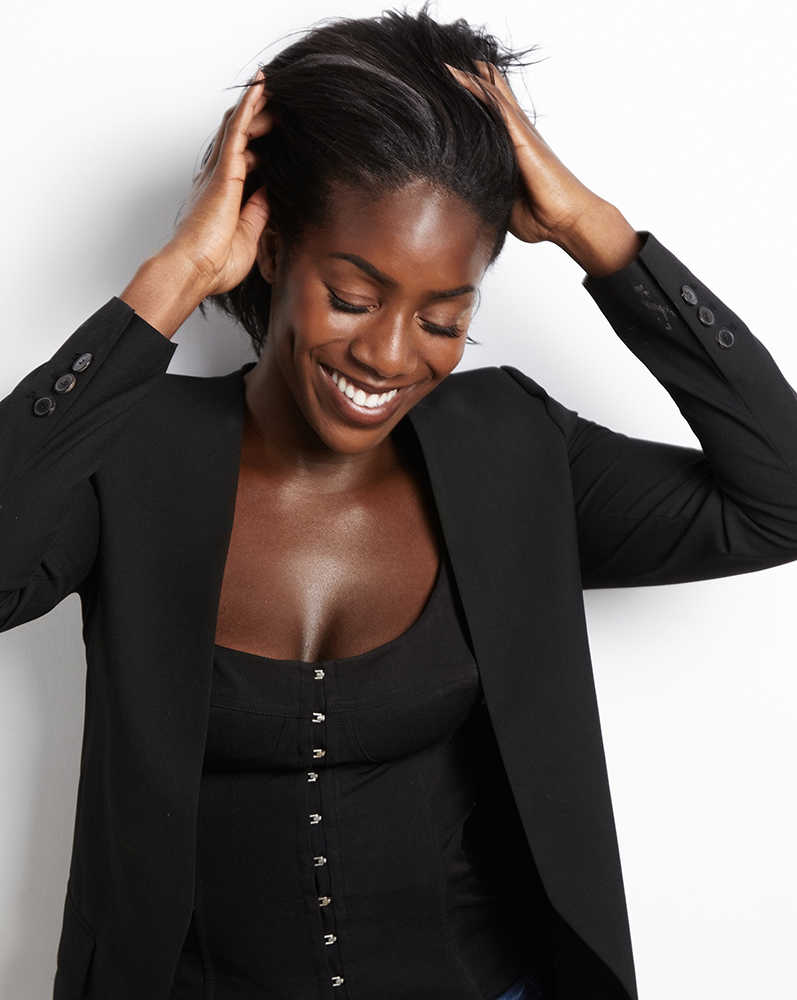 Beautiful, smiling dark skinned woman, hands in her hair