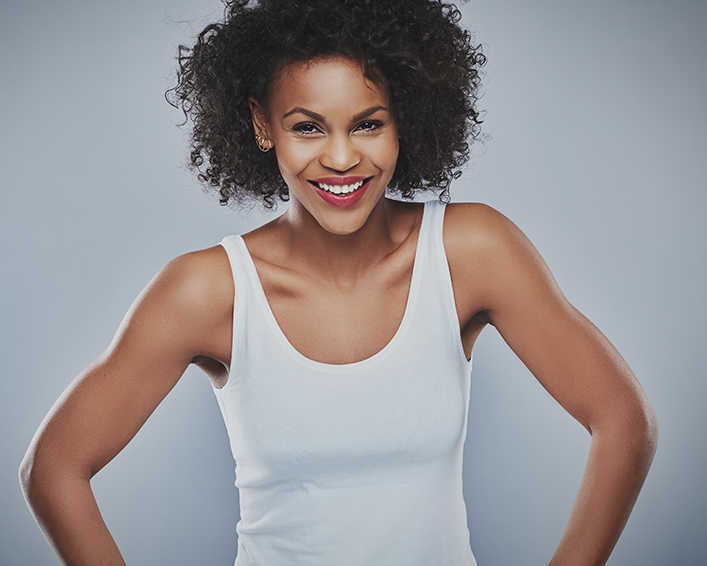 Pretty medium skin tone woman, smiling, hands on hips