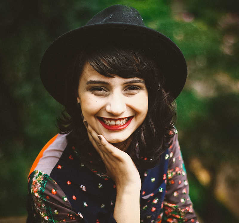 Pretty girl wearing black hat smiling   A Tattoo Removal Patch That Works in 6 AMAZING Ways!   Masterpiece Skin Restoration