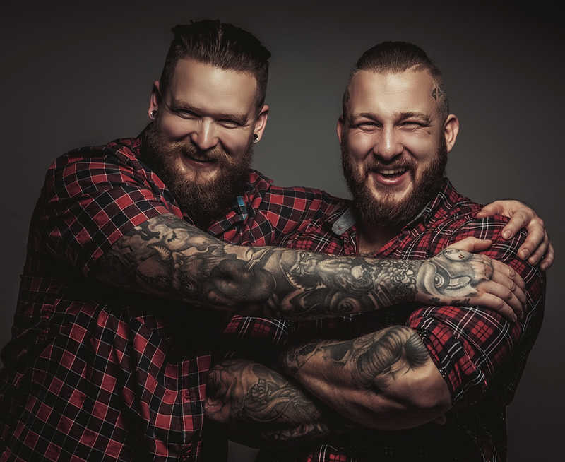 2 heavily tattooed brothers smiling | Tattoo Safety | 13 Ways to Stay Healthy When You Get a Tattoo | Masterpiece Skin Restoration