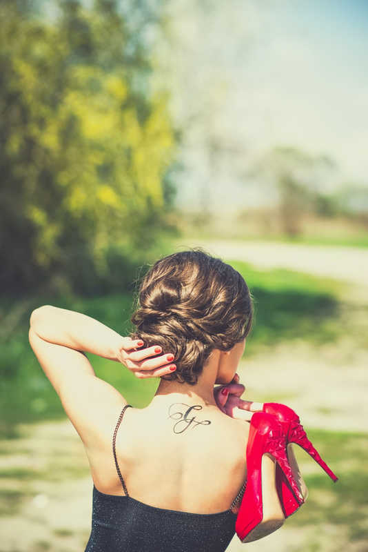 woman with black calligraphy G tattoo on back, red pumps | Tattoo Safety | 13 Ways to Stay Healthy When You Get a Tattoo | Masterpiece Skin Restoration