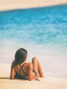 Young woman wearing a black bikini watching waves on the beach | Mesotherapy vs. Liposuction – Which Works Better for Body Contouring? | Masterpiece Skin Restoration