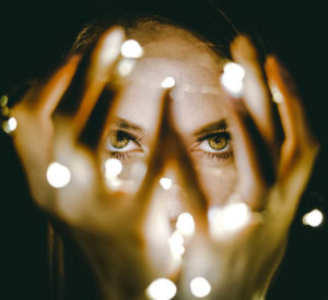 Closeup of woman holding a string of lights in front of her face