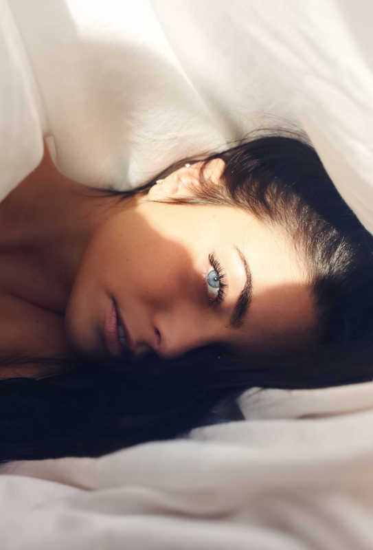 woman with beautiful blue eyes lying in bed | The Keratin Lash Lift vs. a Lash Perm | Which Is Better? | Masterpiece Skin Restoration