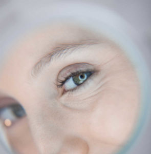 woman's eye reflected in a round mirror | The Keratin Lash Lift vs. a Lash Perm | Which Is Better? | Masterpiece Skin Restoration