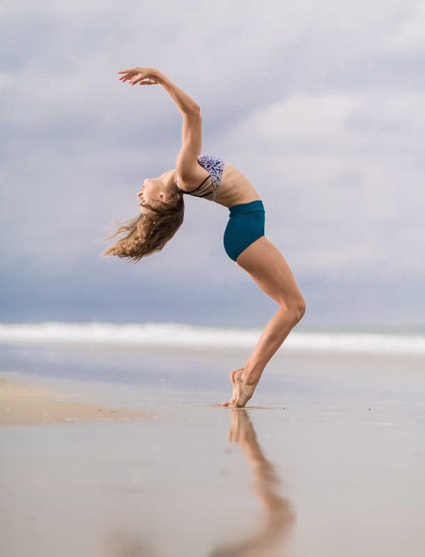 Young woman doing a back flip on the beach | Body Archives | Masterpiece Skin Restoration