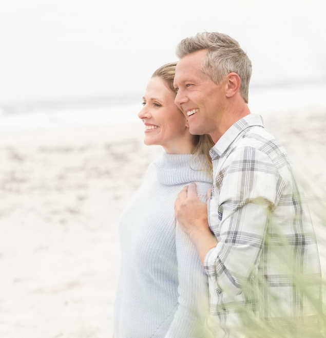 mature couple at the beach looking out at the ocean, smiling | Vaginal Rejuvenation | Why the FDA Says Lasers & Radiofrequency May Not Be Safe | Masterpiece Skin Restoration