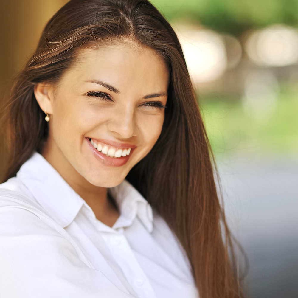 Closeup young woman white shirt medium tone skin smiling | Shop Skincare | Dark Spots | Masterpiece Skin Restoration