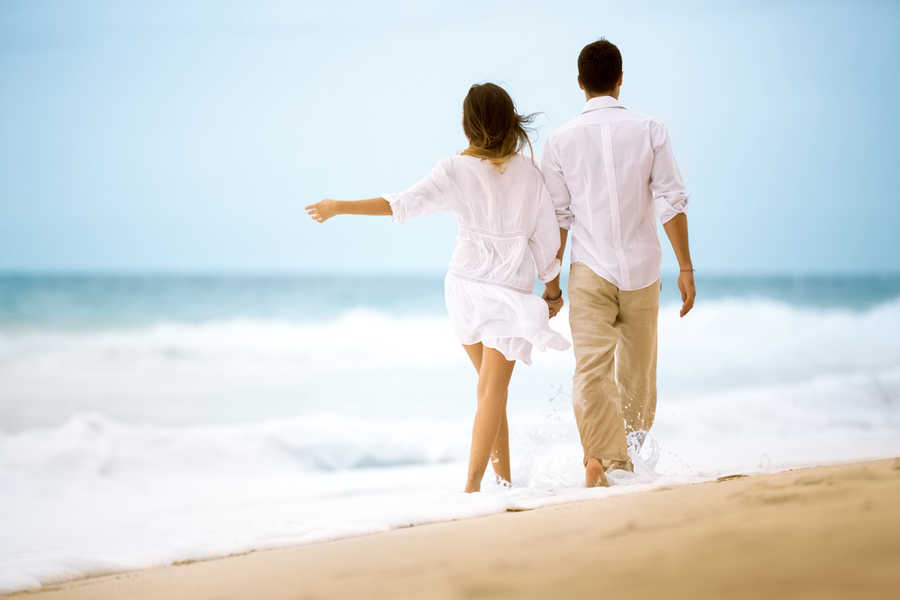 Couple holding hands and walking through the surf | About | Policies | Masterpiece Skin Restoration