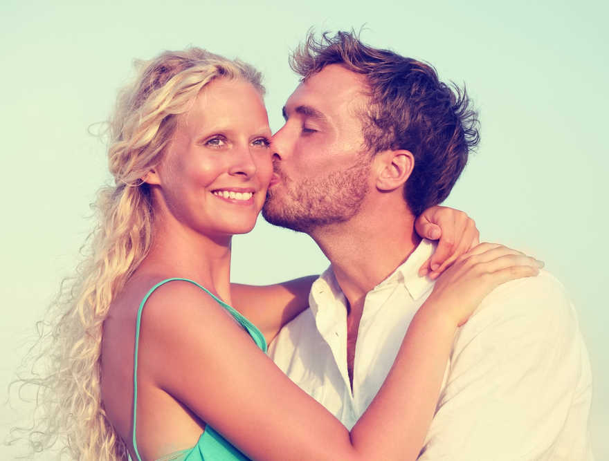 Beautiful woman with long blonde hair getting a kiss on the cheek from her husband
