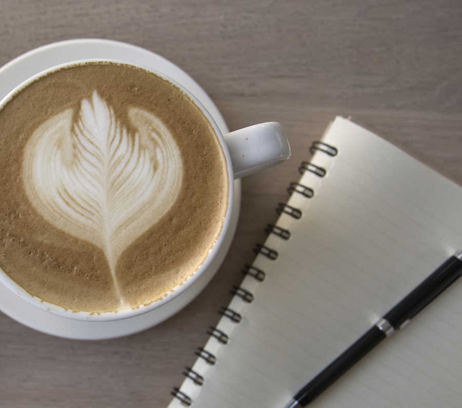 closeup of beautiful coffee drink, notebook, pen | About | Guest Post & Join Our Directory | Masterpiece Skin Restoration