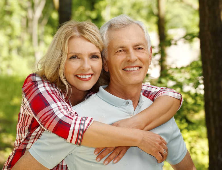 mature woman hugging her huband in the woods | 5 Ways to Treat Spider Veins of the Face | Masterpiece Skin Restoration