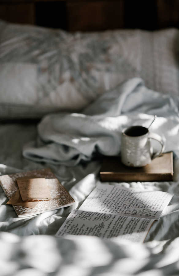 coffee cup, notebook with sunlight streaming onto unmade bed | How to Layer Skincare Products | Shop Products for Wrinkles | Masterpiece Skin Restoration