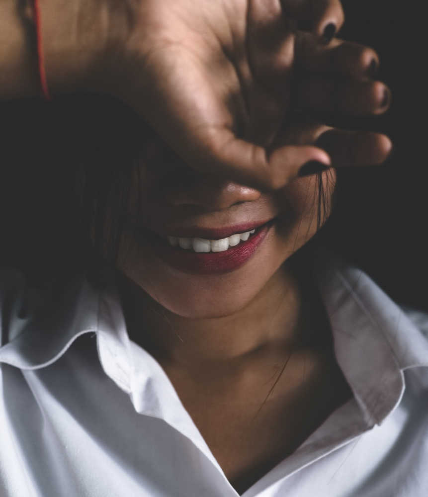 Girl smiling with pretty skin hiding part of her face behind her hand | The Best Skincare Products for Adult Acne | Shop Skincare | Masterpiece Skin Restoration