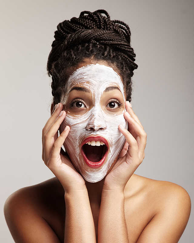 Pretty dark skinned woman with mask on face, hands on face | 9 of the Best Treatments for Dark Skin | Masterpiece Skin Restoration
