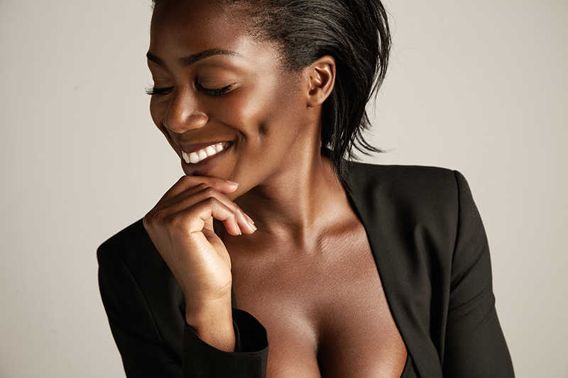 beautiful dark skinned woman smiling, looking to the side, black outfit | 9 of the Best Treatments for Dark Skin | Masterpiece Skin Restoration