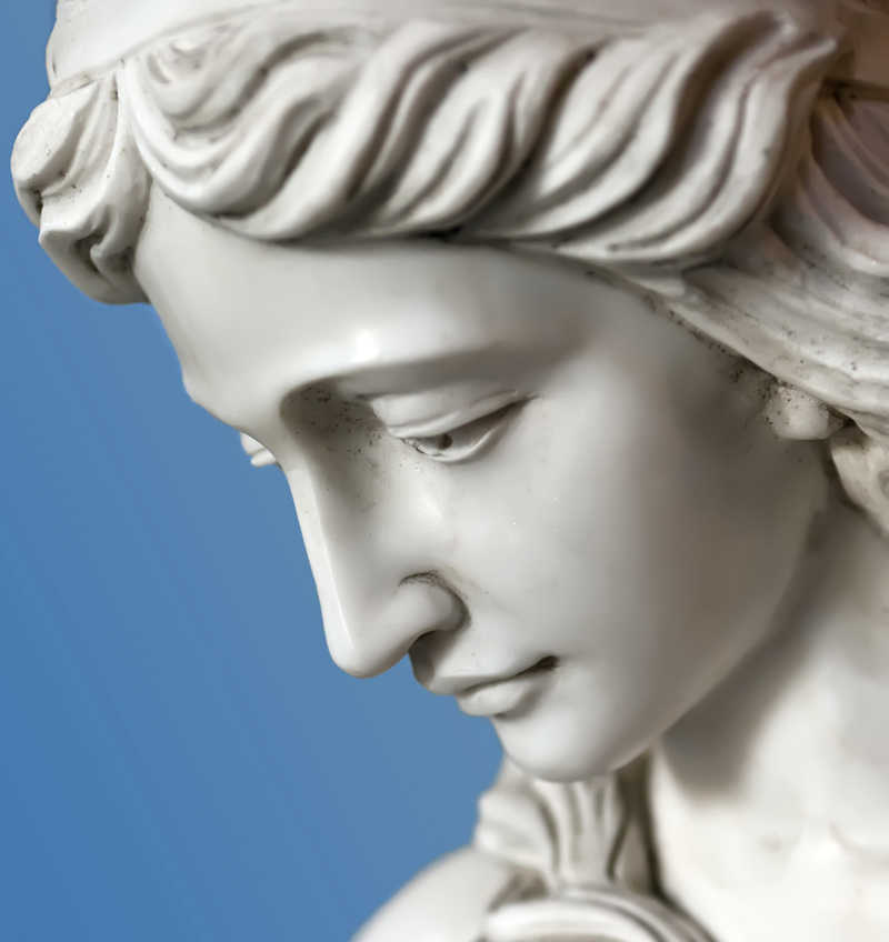 closeup of a beautiful statue of a woman against a blue background | Contact Masterepiece Skin Restoration