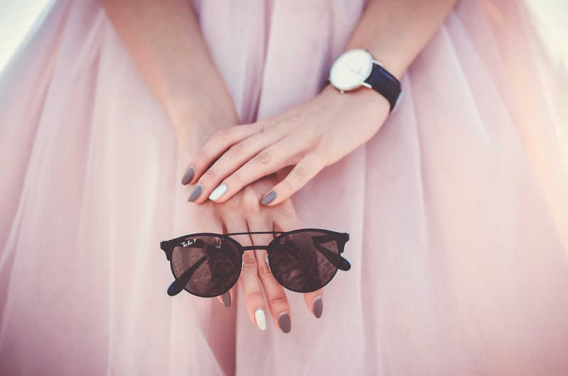 closeup of pink chiffon dress, hands holding sunglasses | How to Get Longer, Stronger Nails + Shop Skincare | Nails | Masterpiece Skin Restoration